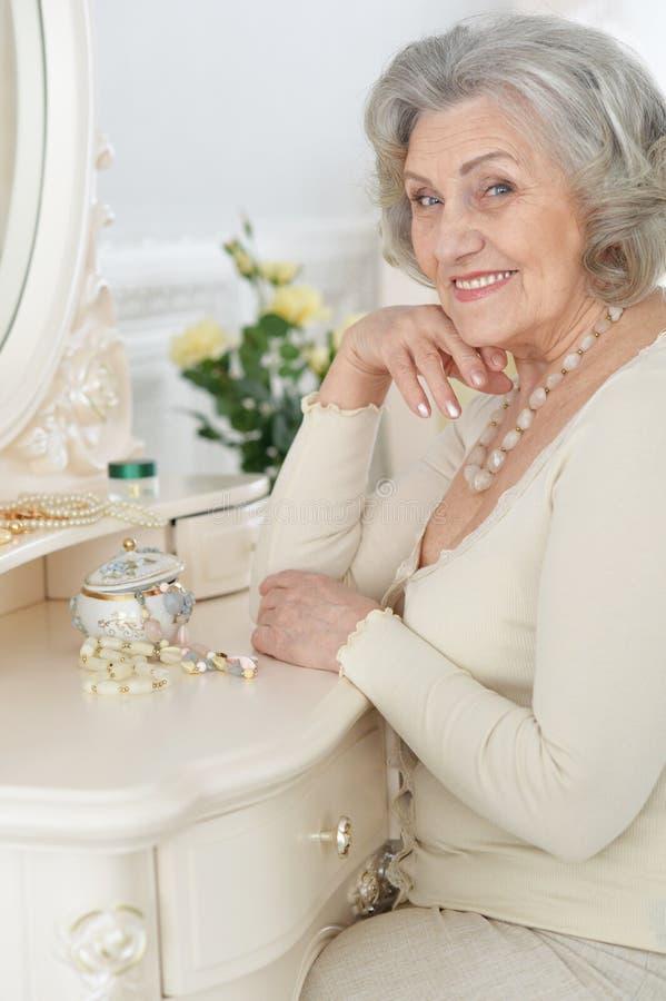 Gelukkige hogere vrouwenzitting dichtbij toilettafel royalty-vrije stock foto's