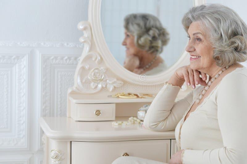 Gelukkige hogere vrouwenzitting dichtbij toilettafel stock afbeeldingen