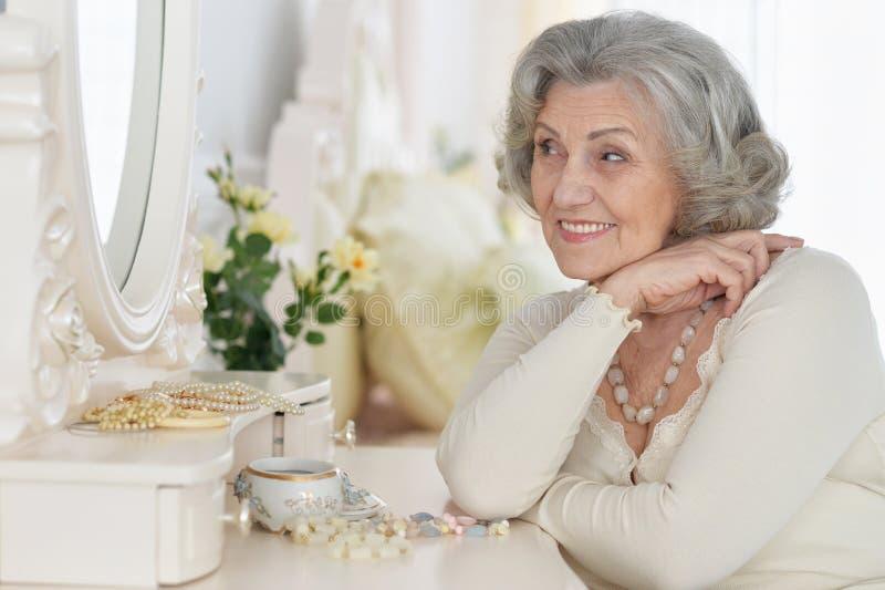 Gelukkige hogere vrouwenzitting dichtbij toilettafel stock afbeelding