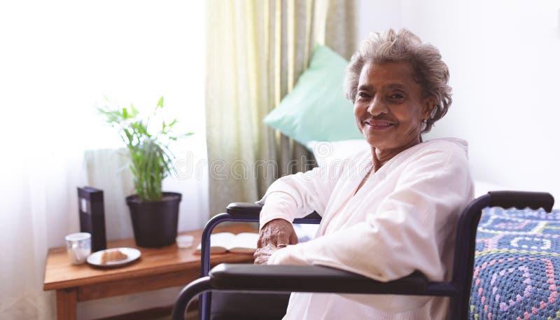 Gelukkige hogere vrouwenzitting in rolstoel bij verpleeghuis stock fotografie