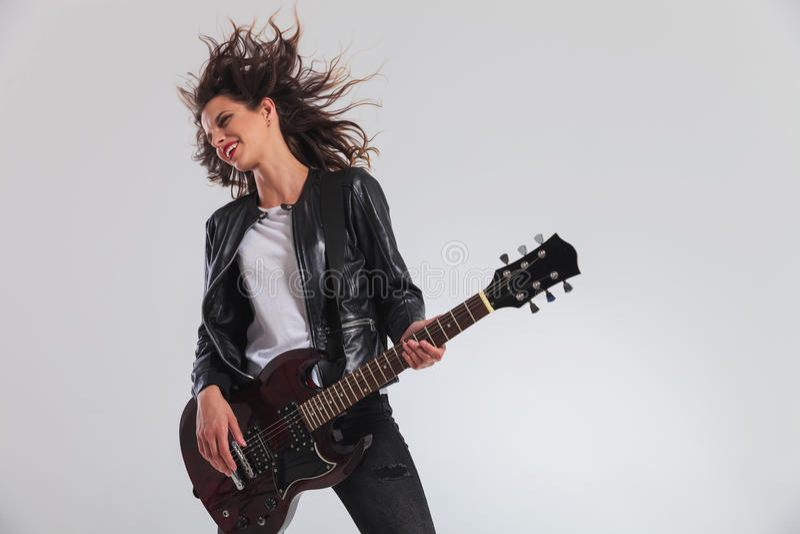 Gelukkige hoofd bonzende vrouwengitarist het spelen gitaar stock foto's