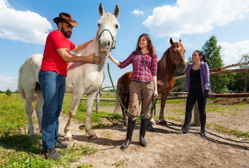 Gelukkige horseback ruiters die rust hebben bij de paddock royalty-vrije stock fotografie