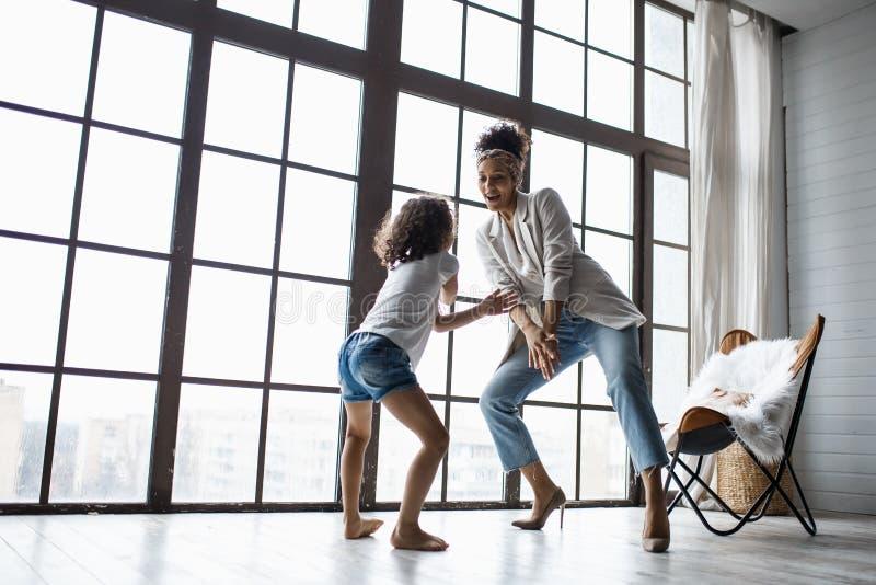Gelukkige houdende van afro Amerikaanse familie Jonge moeder en haar dochter die in het kinderdagverblijf spelen Het mamma en de  stock fotografie