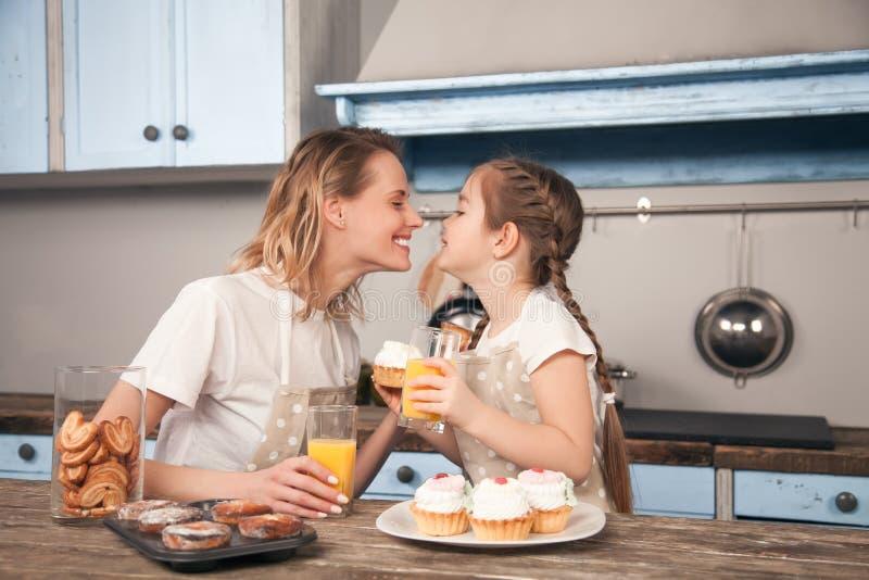 Gelukkige houdende van familie in de keuken Moeder en kind het dochtermeisje eet koekjes die zij en hebbend pret in hebben gemaak stock foto's