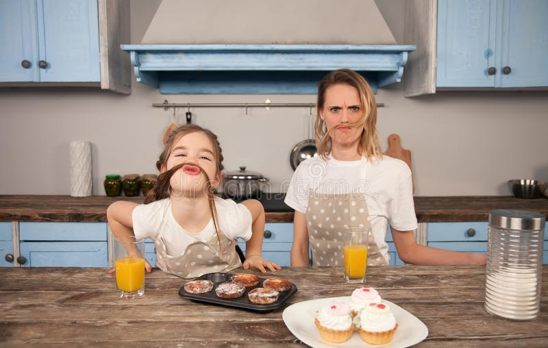 Gelukkige houdende van familie in de keuken Moeder en kind het dochtermeisje eet koekjes die zij en hebbend pret in hebben gemaak stock afbeelding