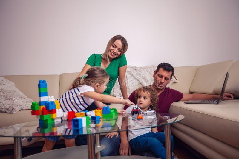 Gelukkige houdende van familie kinderen die met blokkenspeelgoed spelen stock foto's