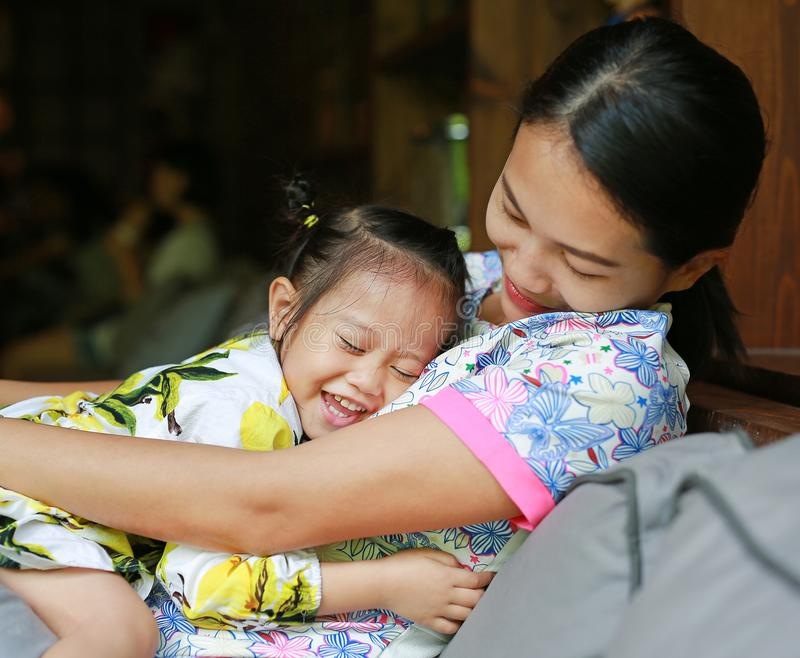 Gelukkige houdende van familie moeder die haar kind op bank koesteren stock afbeelding