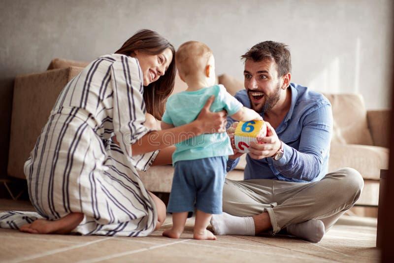 Gelukkige houdende van familie ouders die met haar baby thuis spelen royalty-vrije stock afbeelding