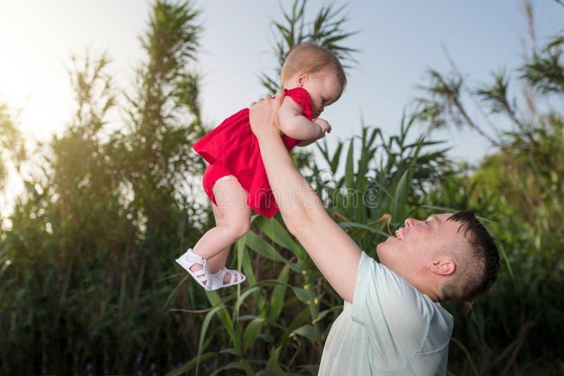 Gelukkige houdende van familie Vader en zijn meisje die en van de dochterbaby in openlucht spelen koesteren royalty-vrije stock foto