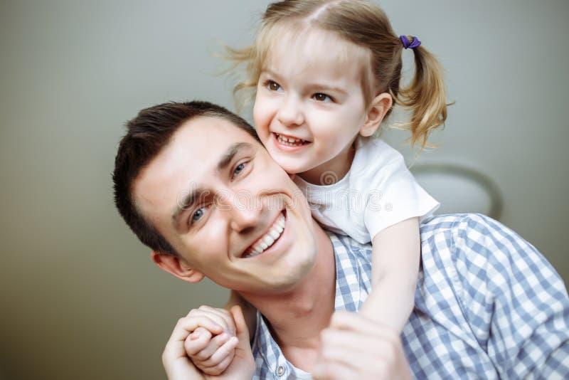 Gelukkige houdende van familie Vader en zijn meisje die en van het dochterkind spelen koesteren Ondiepe Diepte van Gebied stock afbeeldingen