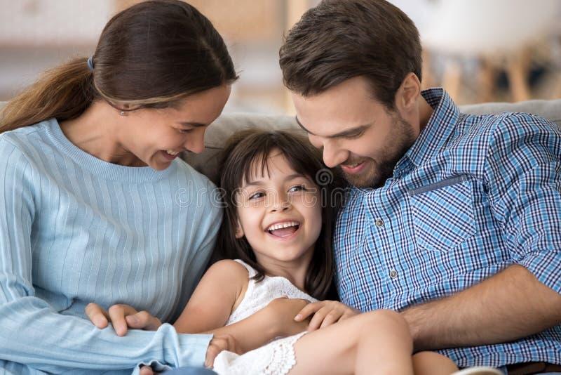 Gelukkige houdende van ouders die jong geitjedochter kietelen die pret het lachen t hebben stock foto