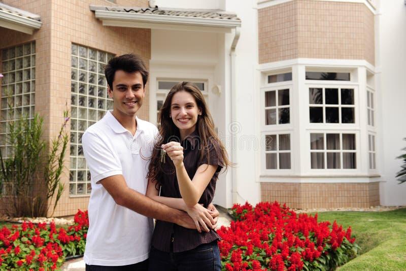 Gelukkige huiseigenaars infront van nieuw huis