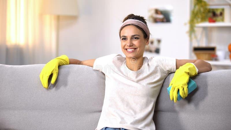 Gelukkige huisvrouw die in handschoenen op bank zitten, die na het ruimte schoonmakende werk ontspannen stock afbeelding