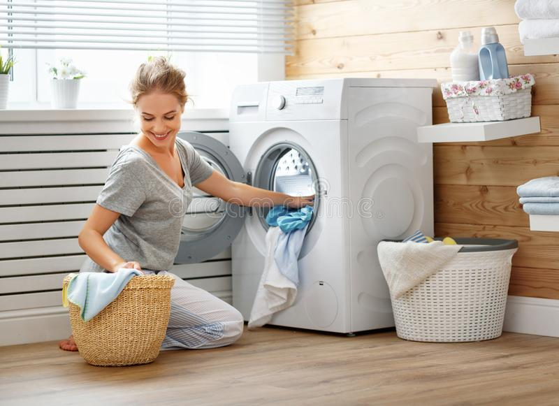 Gelukkige huisvrouwenvrouw in wasserijruimte met wasmachine stock afbeeldingen