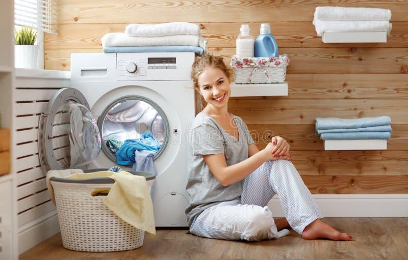 Gelukkige huisvrouwenvrouw in wasserijruimte met wasmachine stock foto's
