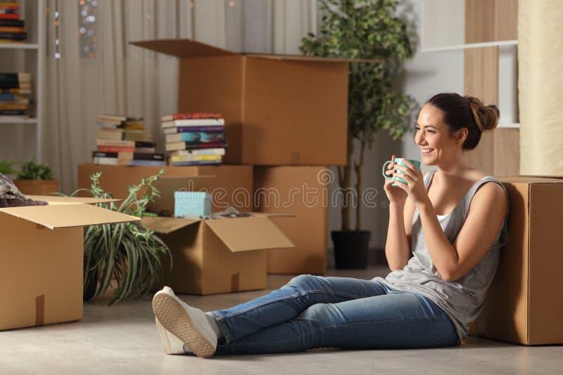 Gelukkige huurder rustende het drinken koffie die zich naar huis beweegt stock afbeelding