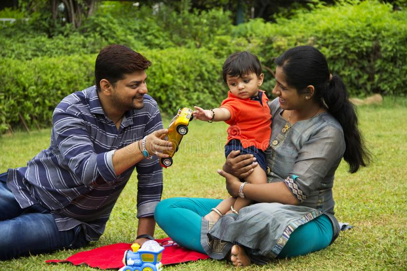 Gelukkige Indische familie, vader die stuk speelgoed auto geven aan zijn peuterzoon, die met zijn moeder, binnen tuin, Pune, Maha royalty-vrije stock afbeeldingen