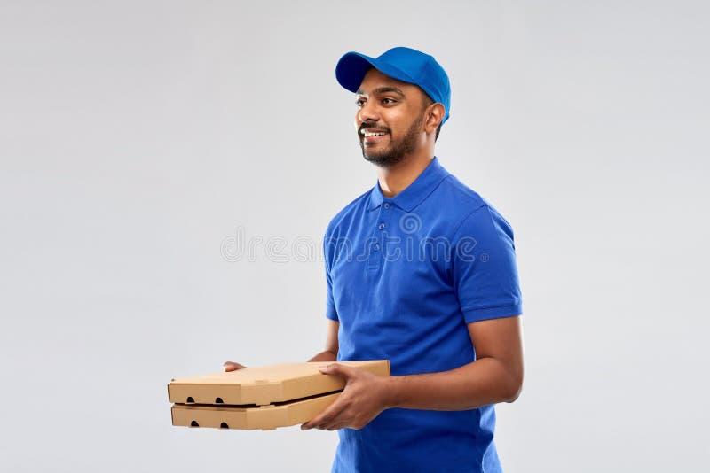 Gelukkige Indische leveringsmens met pizzadozen in blauw royalty-vrije stock afbeelding