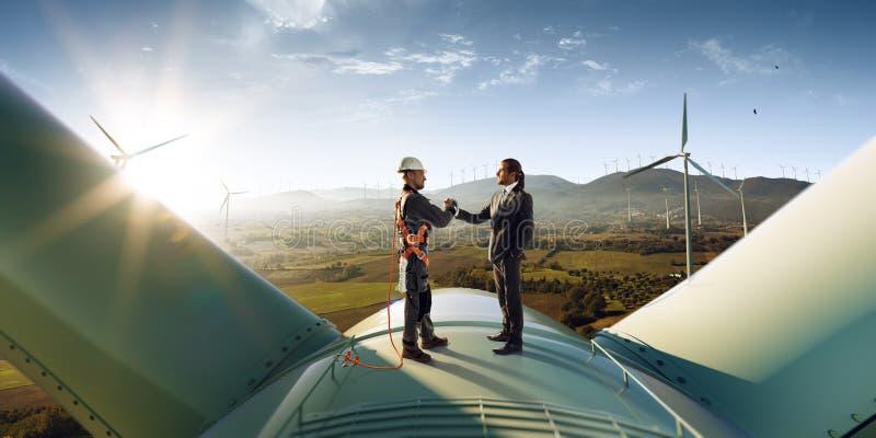 Gelukkige ingenieur en zakenmanschokhanden na het goede werk Zij die een bovenkant van windmolen bevinden zich Rond windgenerator royalty-vrije stock afbeeldingen