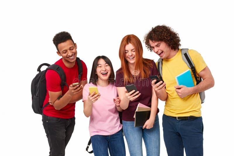 Gelukkige internationale studenten die smartphones gebruiken stock foto's