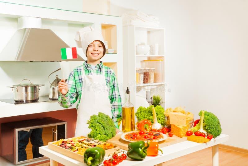 Gelukkige Italiaanse jongen in het eenvormige glimlachen van de kok stock fotografie