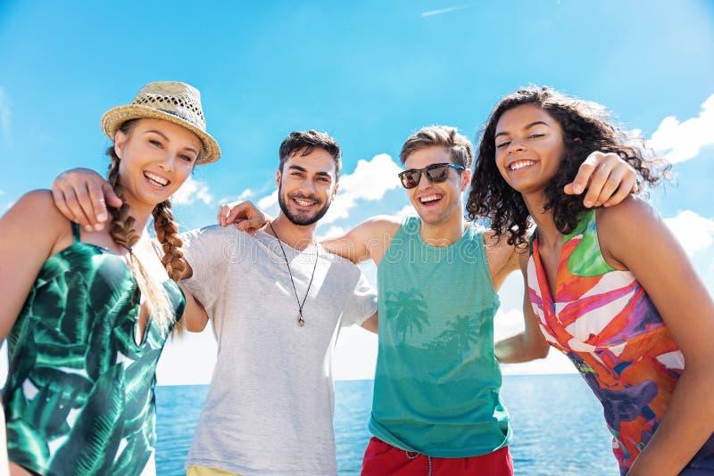 Gelukkige jeugdige meisjes en kerels die op de zomerstrand ontspannen stock foto