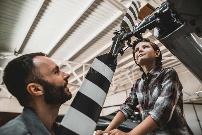 Gelukkige jong geitje en papa die over rotorcrafts vertellen stock fotografie