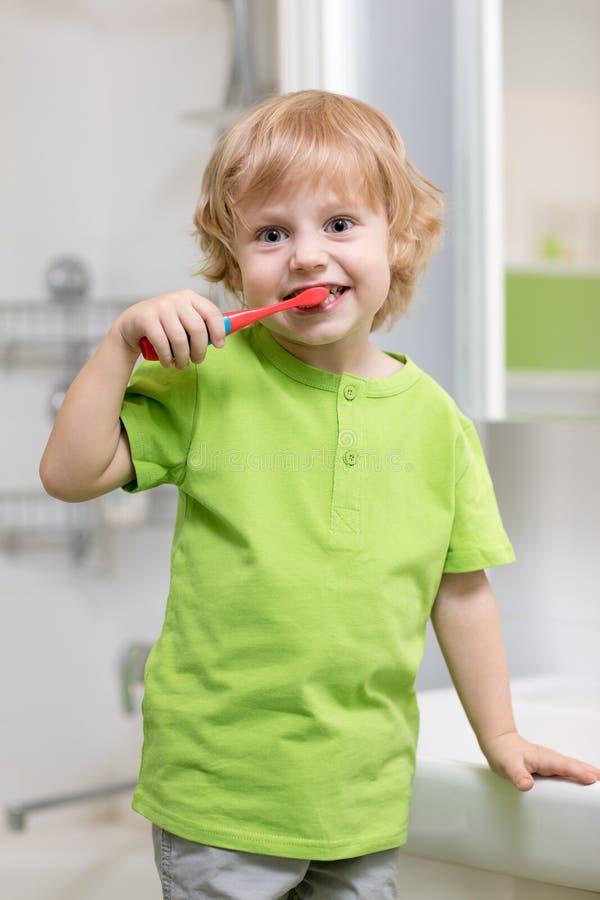 Gelukkige jong geitje of kind het borstelen tanden in badkamers Tand Hygiëne stock afbeeldingen