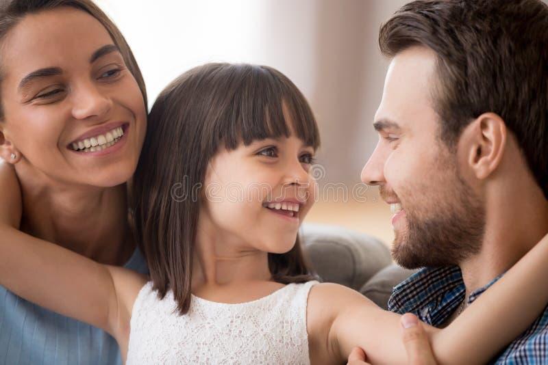 Gelukkige jong geitjedochter die ouders omhelzen die glimlachend mamma bekijken royalty-vrije stock afbeeldingen