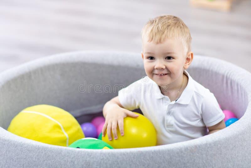 Gelukkige jong geitjejongen die pret binnen in spelcentrum hebben Kind het spelen met kleurrijke ballen in de pool van de speelpl stock fotografie