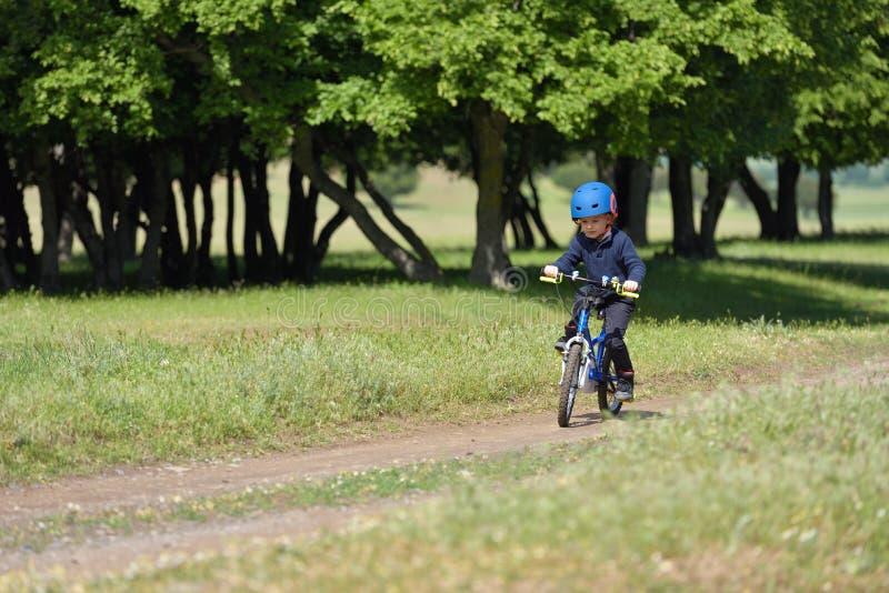 Gelukkige jong geitjejongen van 5 jaar die pret in de lentebos hebben met een bicy stock afbeelding
