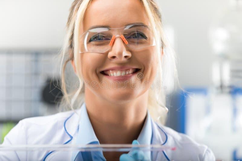 Gelukkige jonge aantrekkelijke glimlachende vrouwenwetenschapper in het laboratorium royalty-vrije stock fotografie