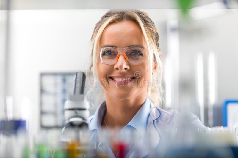 Gelukkige jonge aantrekkelijke glimlachende vrouwenwetenschapper in het laboratorium stock afbeelding