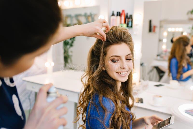 Gelukkige jonge aantrekkelijke vrouw die in kappersalon aan viering voorbereidingen treffen Het maken van modieus kapsel, het gli royalty-vrije stock foto's