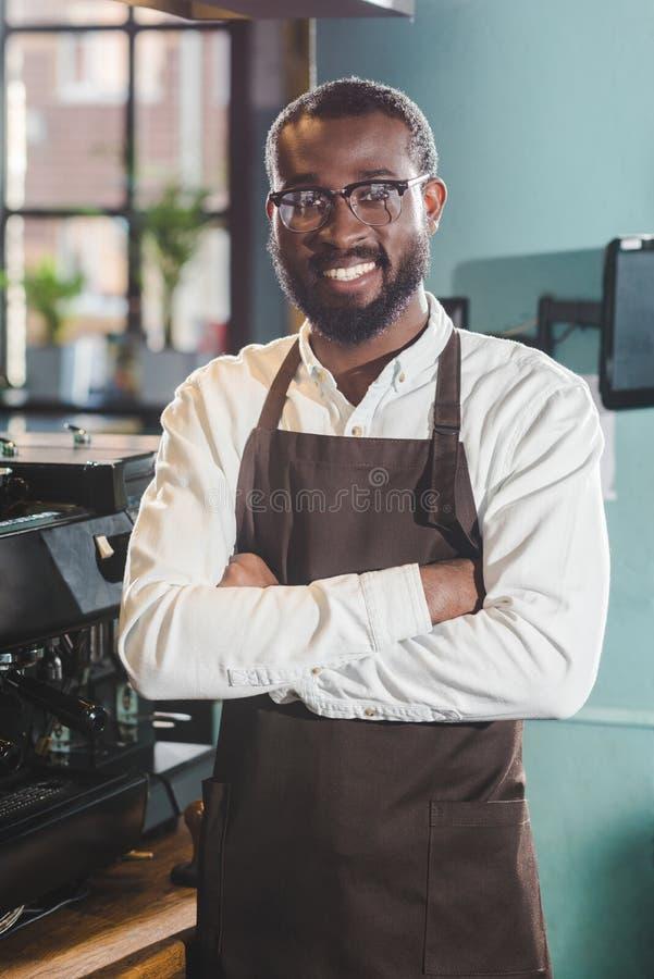 gelukkige jonge Afrikaanse Amerikaanse barista die zich met gekruiste wapens bevinden en bij camera glimlachen royalty-vrije stock afbeelding
