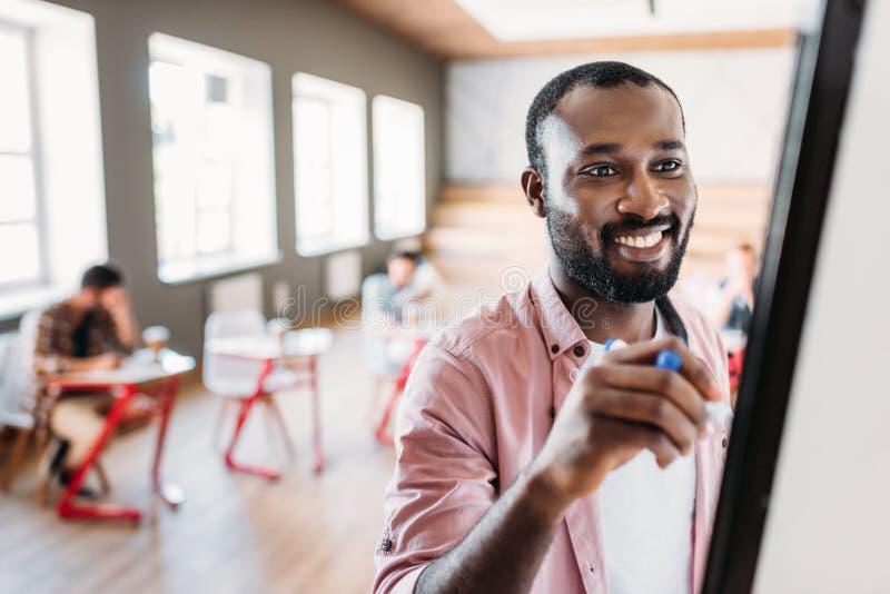 gelukkige jonge Afrikaanse Amerikaanse leraar die op whiteboard bij lezingsruimte schrijven met het vage studenten zitten royalty-vrije stock foto