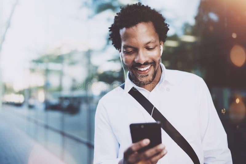 Gelukkige jonge Afrikaanse Amerikaanse mens in hoofdtelefoon die bij zonnige stad loopt en videogesprek met vrienden op van hem m royalty-vrije stock foto's