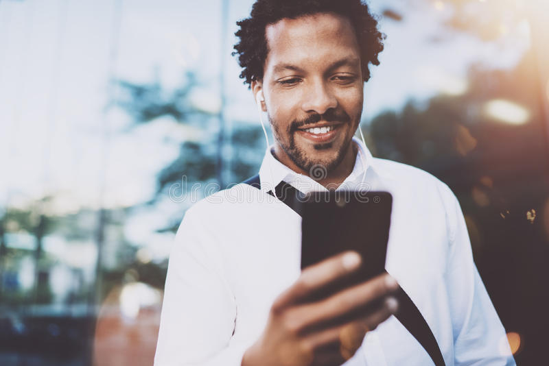 Gelukkige jonge Afrikaanse Amerikaanse mens in hoofdtelefoon die e-maildoos controleren bij zonnige stad en aan muziek op van hem royalty-vrije stock fotografie