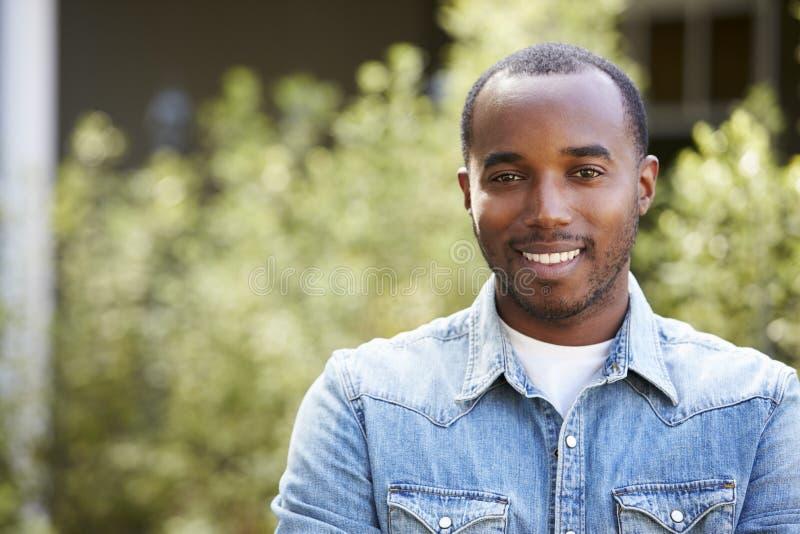 Gelukkige jonge Afrikaanse Amerikaanse mens in horizontaal denimoverhemd, royalty-vrije stock fotografie