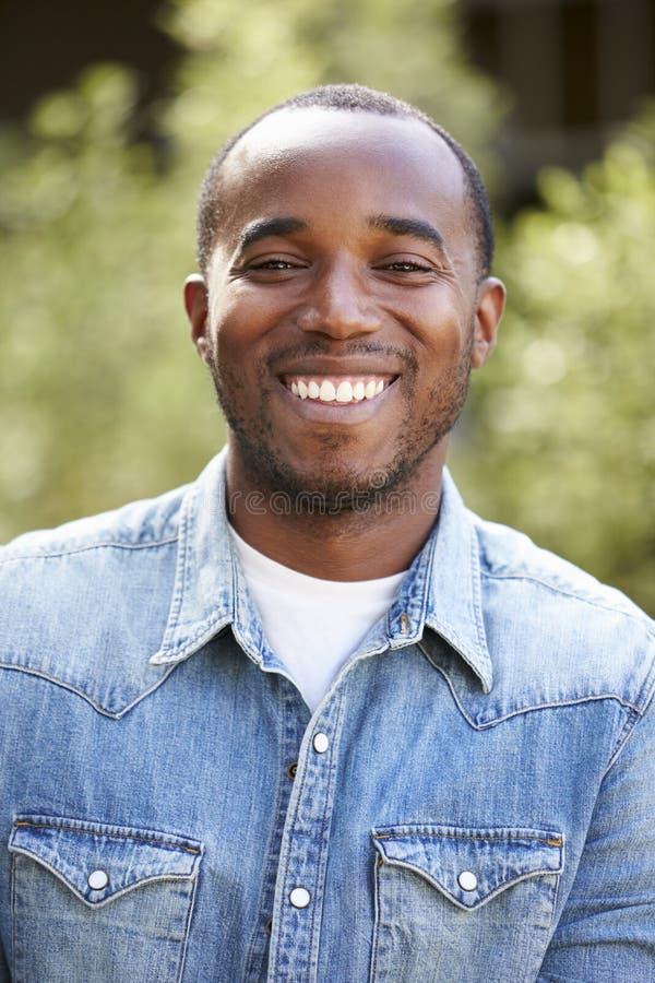 Gelukkige jonge Afrikaanse Amerikaanse mens in verticaal denimoverhemd, royalty-vrije stock afbeeldingen