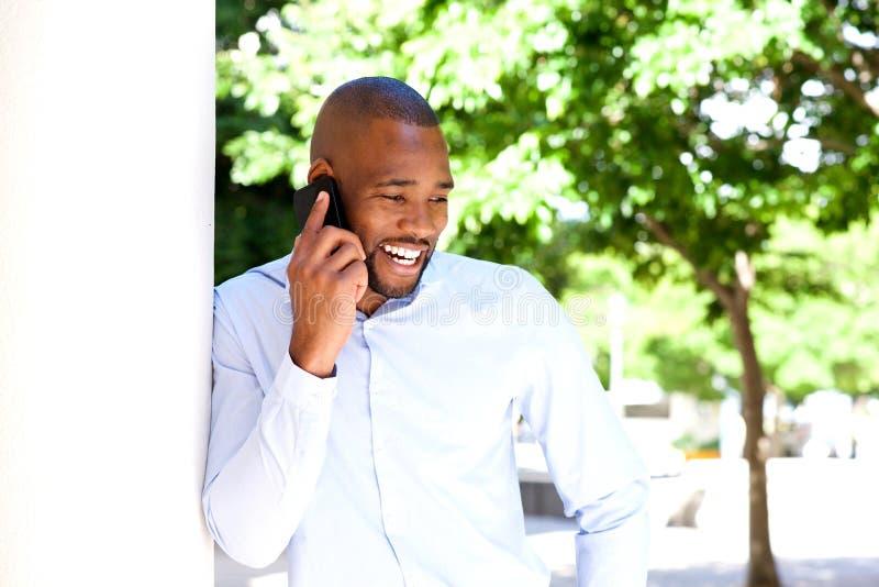 Gelukkige jonge Afrikaanse mens die op mobiele telefoon in openlucht spreken stock foto's