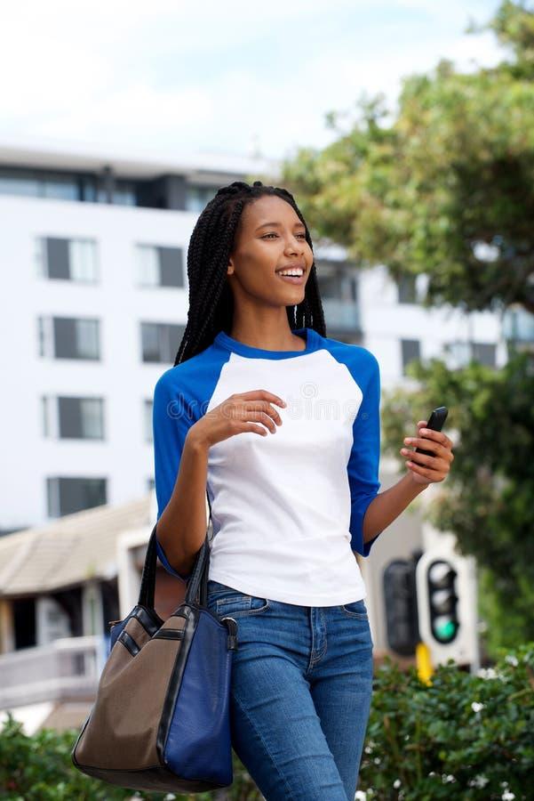 Gelukkige jonge Afrikaanse vrouw die met zak en mobiele telefoon lopen royalty-vrije stock afbeelding