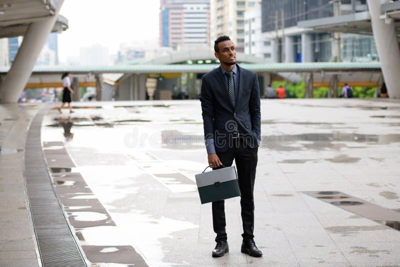 Gelukkige jonge Afrikaanse zakenman die met aktentas in openlucht denken royalty-vrije stock afbeelding