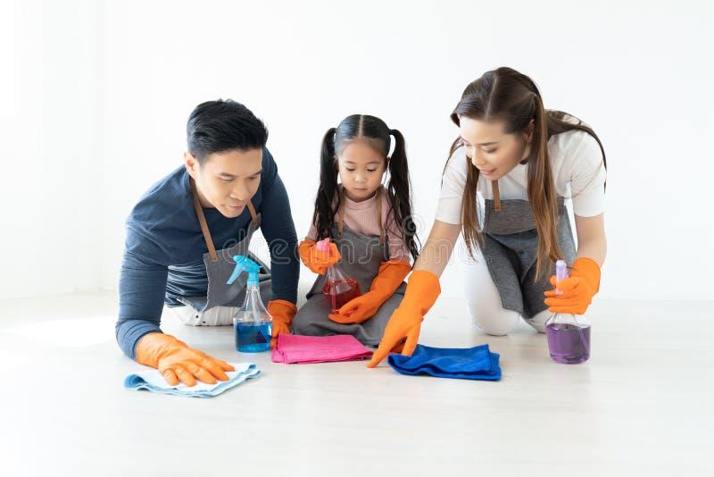 Gelukkige jonge Aziatische familie van drie die hun huis het leven roo schoonmaken stock afbeeldingen