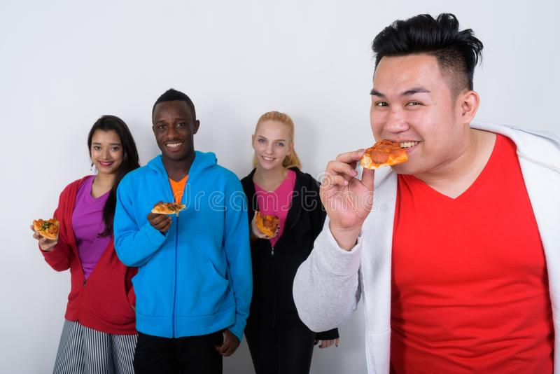 Gelukkige jonge Aziatische mens die plak van pizza met diverse groep o eten stock fotografie