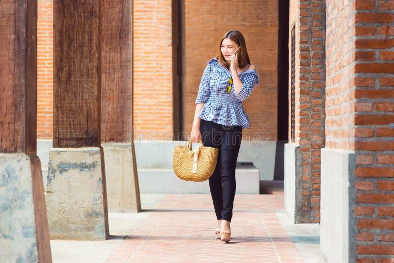 Gelukkige jonge Aziatische vrouw in aardige toevallige en comfortabele kleren w royalty-vrije stock afbeelding