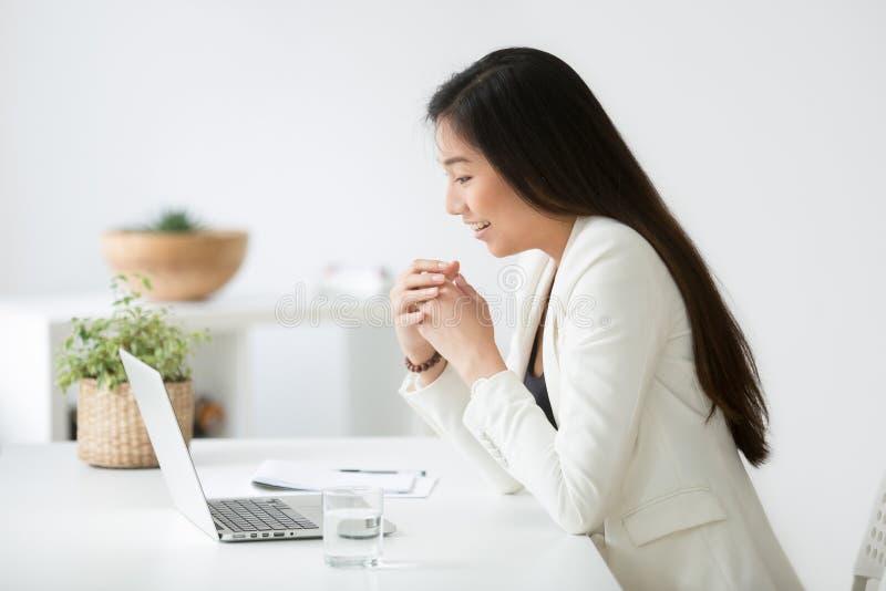 Gelukkige jonge Aziatische vrouw die goed online nieuws op laptop lezen stock foto's