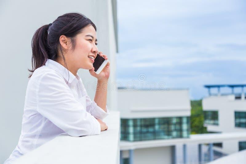 Gelukkige jonge Aziatische vrouw die op de telefoon spreken terwijl status op t stock afbeelding
