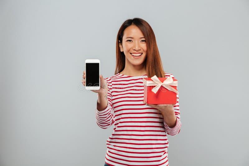 Gelukkige jonge Aziatische vrouw die vertoning van de gift van de telefoonholding tonen stock afbeeldingen