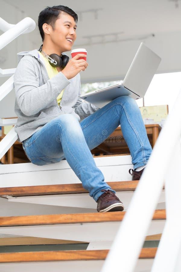 Gelukkige jonge Aziatische werknemer die laptop in een modern bureau met behulp van stock afbeelding